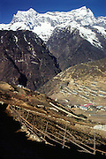 In this 1981 photograph, Namche Bazaar (11,220 feet elevation) was a small village. The mountain of Kongde Ri (sometimes called Kwangde Ri; 20,320 feet elevation) rises 4 kilometers to the west, in the Himalaya of eastern Nepal, Asia.