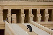 "A caretaker sweeps dusty steps at the ancient Egyptian Temple of Hatshepsut near the Valley of the Kings, Luxor, Nile Valley, Egypt. The Mortuary Temple of Queen Hatshepsut, the Djeser-Djeseru, is located beneath cliffs at Deir el Bahari (""the Northern Monastery""). The mortuary temple is dedicated to the sun god Amon-Ra and is considered one of the ""incomparable monuments of ancient Egypt."" The temple was the site of the massacre of 62 people, mostly tourists, by Islamists on 17 November 1997."