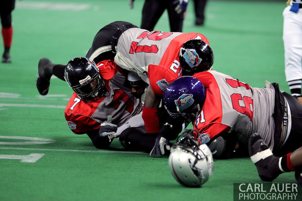 6-28-2007: Anchorage, AK - Sandwiched between Barracuda defenders Rolandus Johnson(7), Roderick Knight (21), and Jody Cantu (61), Alaska's Thomas Ford Jr.has his helmet popped off as he gained a first down in the Alaska Wild 47 to 53 loss to the CenTex Barracudas at the Sullivan Arena.