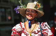 """Woman with flamenco dress under the shade of her hat. The pilgrim route of the Hermandade de Sanlucar de Barrameda from Sanlucar across the Parque Donana to El Rocio, Huelva Province, Andalusia, Spain...El Rocio follows on from Semana Santa - Easter week and the various spring ferias, of which Seville's Feria de Abril (April) is the biggest. The processions to the (Hermitage) Hermita de El Rocío, at Pentecost, is the most famous (Romeria) pilgrimage in the Andalusian region, attracting nearly a million people from across Andalusia, Spain and the world. The cult started off in the 13th century when a statue of the virgin Mary was apparently found in a tree trunk in the Donana Park. What was first a local devotion at Pentecost by local pilgrim brotherhoods """"hermandades"""" became by the 19th century into dozens of fraternities developed from such as Cadiz, Selville and Huelva. Some walk for several days, others travel with oxen drawn wagons or on horseback, with traction engines and all terrain vehicles, camping along the trail they take. They wear Andalusian costumes, tight breeches, boots, short jackets and frilly flamenco skirts. Many festivities, flamenco dance, laments, songs and music are combined with religious prayers. Devout pilgrims walk as a penance, keeping vows of silence. An emblem of the immaculate conception (sin peche) is carried. On the Pentecost after the stroke of midnight on the whit Sunday the virgin Mary is carried from the church through the streets of El Rocio by each hermandade to visit each brotherhood's shrine."""