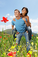 Young couple standing in mountain meadow man giving woman piggy back front view