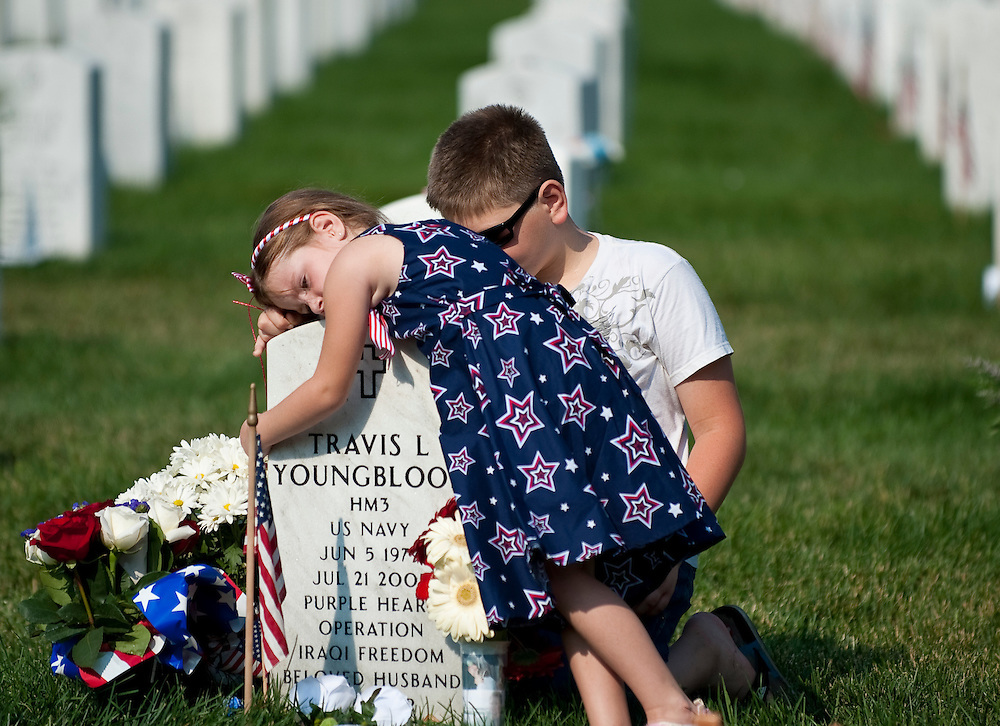 May 31, 2010 - Washington, District of Columbia, U.S., - Emma Youngblood hungs her father's headstone as her brother,  Hunter sits nearby during a vistit to Section 60 at Arlington National Cemerery on Memorial day. (Credit Image: © Pete Marovich/ZUMA Press)