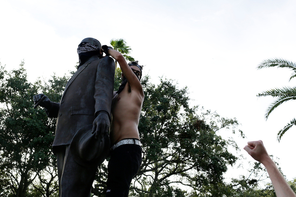Protestor Andrew Speirs, ties a bandana over a statue in Ybor City during the 2012 Republican National Convention in Tampa, Fla. on Aug. 28, 2012. Photo by Greg Kahn