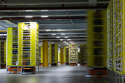 "© Licensed to London News Pictures . 04/12/2019. Manchester , UK . Robotic stock trucks shift products around a central unit within the warehouse . Inside the ""MAN1"" Amazon fulfilment centre warehouse at Manchester Airport in the North West of England . Photo credit : Joel Goodman/LNP"