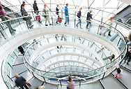 Large group of people walking down a spiral staircase.<br />