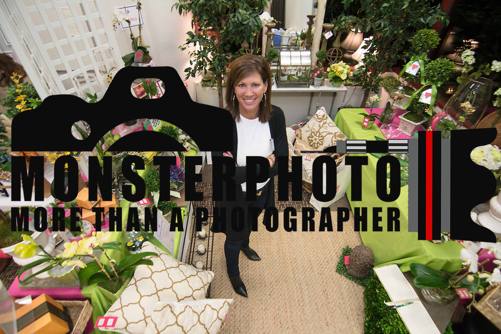 Patty McCoy pose for a photo at her Petals flowers and fine gifts booth during the 3rd Annual Guilty Girls Warehouse Sale Friday, Feb. 06, 2015 at University of Delaware's Arsht Hall in Wilmington, DE.