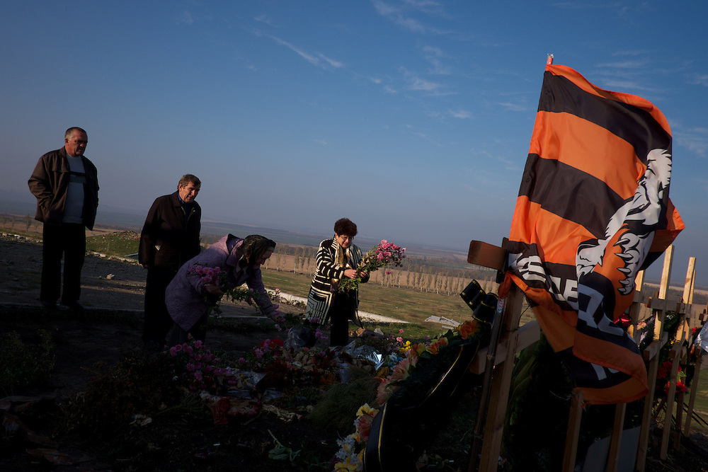SNIZHNE, UKRAINE - OCTOBER 17, 2014: A group of visitors deposit crowns of flowers at the burial site of seven rebel fighters from Vostok battalion killed during fierce fighting against the Ukrainian National Guard in the control for Savur-Mohyla, a strategic highest point in Donetsk region. CREDIT: Paulo Nunes dos Santos
