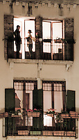A couple are standing and talking in a window in an old building in Venice, Italy.