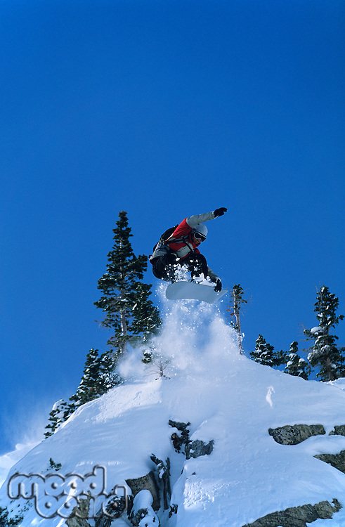 Snowboarder jumping from mountain ledge