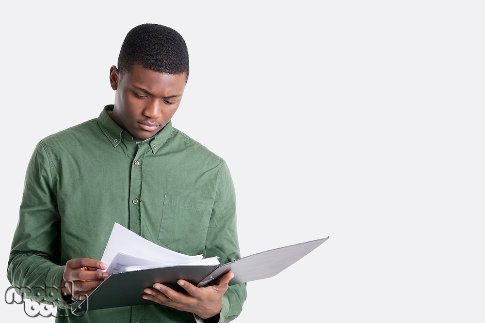 Young African American man reading documents over gray background