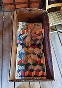A doll and quilt rest in a wood cradle at Humpback Rocks Mountain Farm, a restored 1890s farmstead open to the public at Milepost 5.8 on the Blue Ridge Parkway, in Virginia, in the Blue Ridge Mountains (a subset of the Appalachian Mountains), USA. In summer, costumed interpreters demonstrate 1890s southern Appalachian mountain life. European settlers of the Appalachian Mountains forged a living from abundant native materials: hickory, chestnut, and oak trees provided nuts for food, logs for building, and tannin for curing hides; and the rocks were used as foundations, chimneys and stone fences. This farm was originally a Land Grant tract dispensed by the Commonwealth of Virginia to induce pioneers to settle; and later it became known as the William J. Carter Farm. The scenic 469-mile Blue Ridge Parkway was built 1935-1987 to aesthetically connect Shenandoah National Park (in Virginia) with Great Smoky Mountains National Park in North Carolina, following crestlines and the Appalachian Trail.