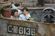 """A North Korean boat workersin the river town of Sinuiju July 8, 2006. China and North Korea are separated by the Yalu River, upon which Chinese tourists take pleaure cruises across the water to  observe their less economically developed neighbors.  North Korea has threatened to take """"stronger physical actions"""" after Japan imposed punitive measures in response to its barrage of missile tests and pushed for international sanctions. North Korea has vowed to carry out more launches and has said it will use force if the international community tries to stop it. DPRK, north korea, china, dandong, border, liaoning, democratic, people's, rebiblic, of, korea, nuclear, test, rice, japan, arms, race, weapons, stalinist, communist, kin jong il"""