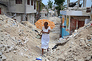A woman walking through the destruction in a neighborhood called Del Mas 32 near the makeshift refugee camp, JP HRO, run by the movie actor Sean Penn in Port-au-Prince, Haiti on July 16, 2010.<br /> The camp is estimated to have over 55,000 refugees. <br /> Six month after a catastrophic earthquake measuring 7.3 on the Richter scale hit Haiti on January 13, 2010, killing an estimated 230,000 people, injuring an estimated 300,000 and making homeless an estimated 1,000,000.