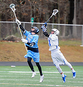 Bedford High School senior Timothy Regan leaps to try and take the ball from Triton freshman Daniel Groder during the game in Bedford, April 19, 2018. Bedford fell to Triton, 12-6.   [Wicked Local Photo/James Jesson]