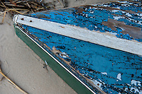 Boat on the beach with worn blue paint on the hull.