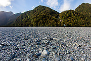 A woman walks across a vast basin of smooth river rock on the South Island of New Zealand