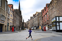 Edinburgh, Scotland, UK. 18 April 2020. Views of empty streets and members of the public outside on another Saturday during the coronavirus lockdown in Edinburgh. Woman running on a deserted Royal Mile.  Iain Masterton/Alamy Live News