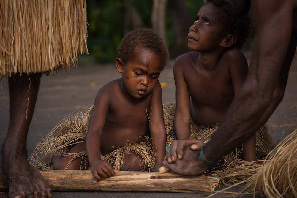 Young children are looking into the camera while older men are busy making a fire, Tannah, Vanuatu.