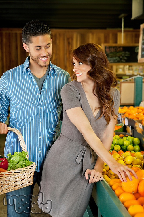 Beautiful young couple shopping together in market