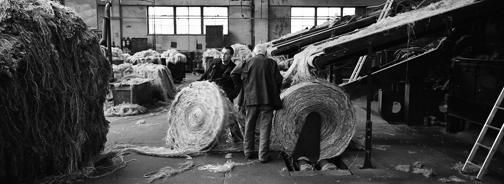 Two workers handling circular bales of jute at Tay Spinners mill in Dundee, Scotland. This factory was the last jute spinning mill in Europe when it closed for the final time in 1998. The city of Dundee had been famous throughout history for the three 'Js' - jute, jam and journalism.
