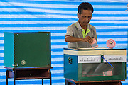 03 MARCH 2013 - BANGKOK, THAILAND: . A man drops his completed ballot into the ballot box at a polling place in Benchasiri Park in Bangkok. Bangkok residents went to the polls Sunday to elect a new governor. Voter turnout was expected to be heavy for a local election. Pongsapat Pongchareon, the Pheu Thai candidate is thought to hold a slight lead over Sukhumbhand Paribatra, the Democrats' candidate. There are a total of 25 candidates in the election but only Pheu Thai and the Democrats are given a chance of winning.    PHOTO BY JACK KURTZ