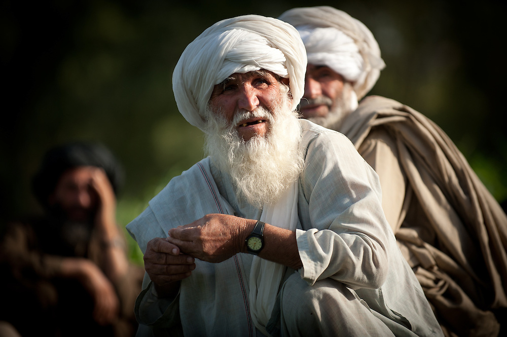 An elderly Afghan villager waits while Marines question his companions.