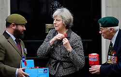 ©  London News Pictures. 31/10/2016. London, UK. British prime minister THERESA MAY struggles to attached  a poppy as she meets veterans involved in the Royal British Legion on the steps of 10 Downing Street to donate to the Poppy Appeal. The Poppy Appeal raises funds for the armed forces  by selling red poppies that are worn around remembrance Sunday, to remember fallen Service men and women killed in conflict. L to R Veteran, STEWART HARRIS (32), THERESA MAY and Veteran ROY MILLER (92). Photo credit: Ben Cawthra/LNP