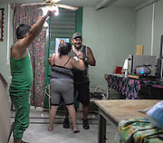 With loud salsa music blaring from the radio, a couple dances in their small Centro Habana home.