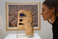 "© Licensed to London News Pictures. 12/05/2017. London, UK.   A staff member views ""Bomboy"", 1978-79, by El Anatsui (Ghana) (Est. GBP 30-50k) at the preview for the first sale dedicated to Modern and Contemporary African Art at Sotheby's New Bond Street.  The sale features over 115 artworks by over 60 different artists from 14 countries across the continent. Photo credit : Stephen Chung/LNP"