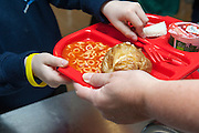 A young child at a UK primary school is handed a school dinner including a jacket potato and spaghetti hoops on a red plastic tray.