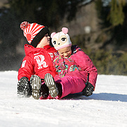 A young girl and boy sledding in Central Park after New York City was hit with over 7 inches of snow during its first winter storm of the year. Central Park, Manhattan, New York, USA. 4th January 2014 Photo Tim Clayton