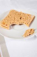 Peanut butter on slice of bitten bread