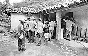 Lenca men weighing seed corn in their rural mountain village of Las Hortencias, Honduras.