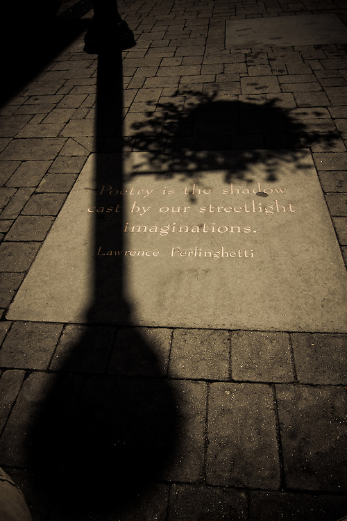 A quote from Lawrence Ferlinghetti is permanently engrained on the sidewalk beside the City Lights Bookstore, North Beach, San Francisco, California, USA.