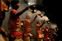 """Hindu holy men perform a """"puja"""" which is a ceremony to their gods, along India's Ganges River in their holiest city, Varanasi (formerly Banaras). Varanasi is principally known to travelers for its ghats (stone steps leading directly into the water). Most ghats are used for ritual bathing. Hindu pilgrims, while standing waist high in the water, pray to cleanse their souls as they face the rising sun.<br /> Varanasi also has cremation ghats because Hindus believe that those who die and are cremated in Varanasi go directly to heaven, bypassing the lengthy reincarnation process. First the dead are burned on riverside pyres, then their ashes are scattered on the sacred Ganges River."""