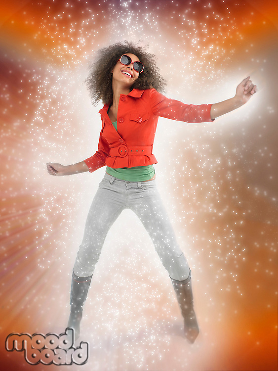 Woman with curly hair wearing sunglasses dancing with lighting effect