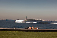 New York. a man sleeping in front of, Hudson river and statue of liberty  view from  Battery park  New York  Usa /   Hudson river et statue de la liberte vue depuis Battery park  New York  USa