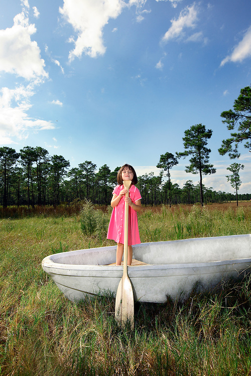 A girl plays on a boat in the middle of a field.