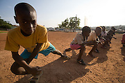 Boys stretch their legs prior to a football practice in Accra, Ghana.