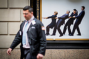 A floor specialist, stock broker, walks past an ad for the NYSC New York Sports Club. This particular NYSC gym is on Wall Street, right next to the NYSE Euronext Stock Exchange.
