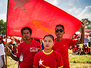 01 NOVEMBER 2015 - YANGON, MYANMAR: People use a NLD flag for shade at the NLD's last election rally of the 2015  election in the Yangon suburbs Sunday. Political parties are wrapping up their campaigns in Myanmar (Burma). National elections are scheduled for Sunday Nov. 8. The two principal parties are the National League for Democracy (NLD), the party of democracy icon and Nobel Peace Prize winner Aung San Suu Kyi, and the ruling Union Solidarity and Development Party (USDP), led by incumbent President Thein Sein. There are more than 30 parties campaigning for national and local offices.    PHOTO BY JACK KURTZ