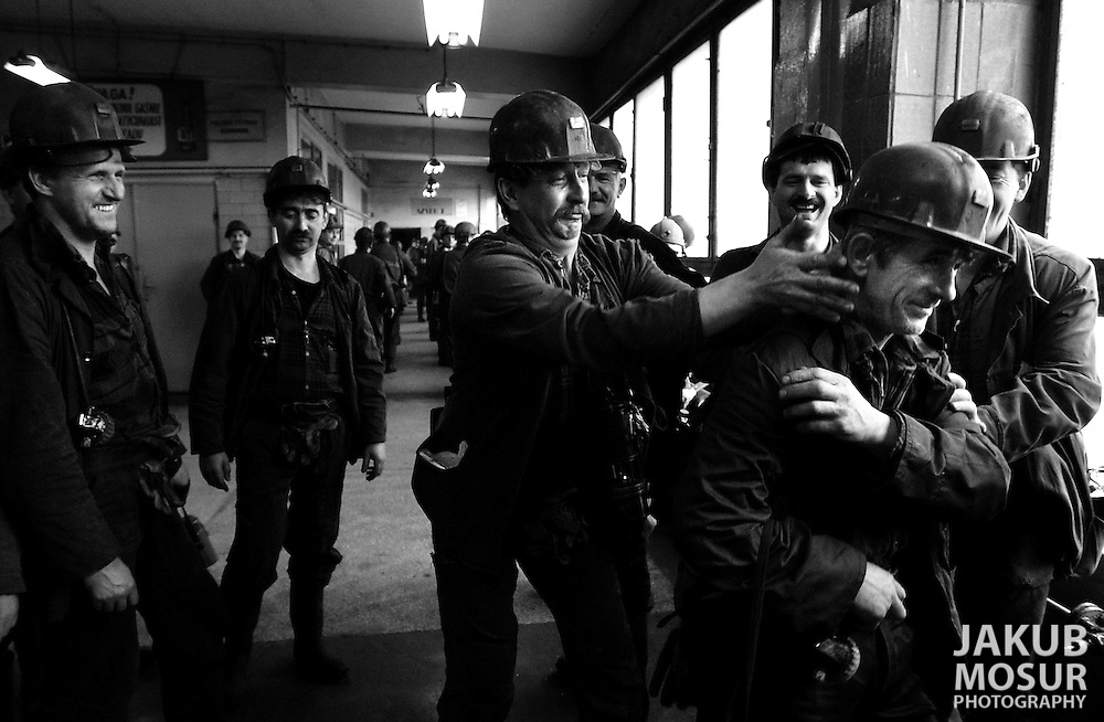 Coalminers tease each other while waiting to go down elevators into the the Piast Coalmine for an 8 hour shift 650 meters under the ground in Bierun, Poland on April 10, 2002..Photo by Jakub Mosur
