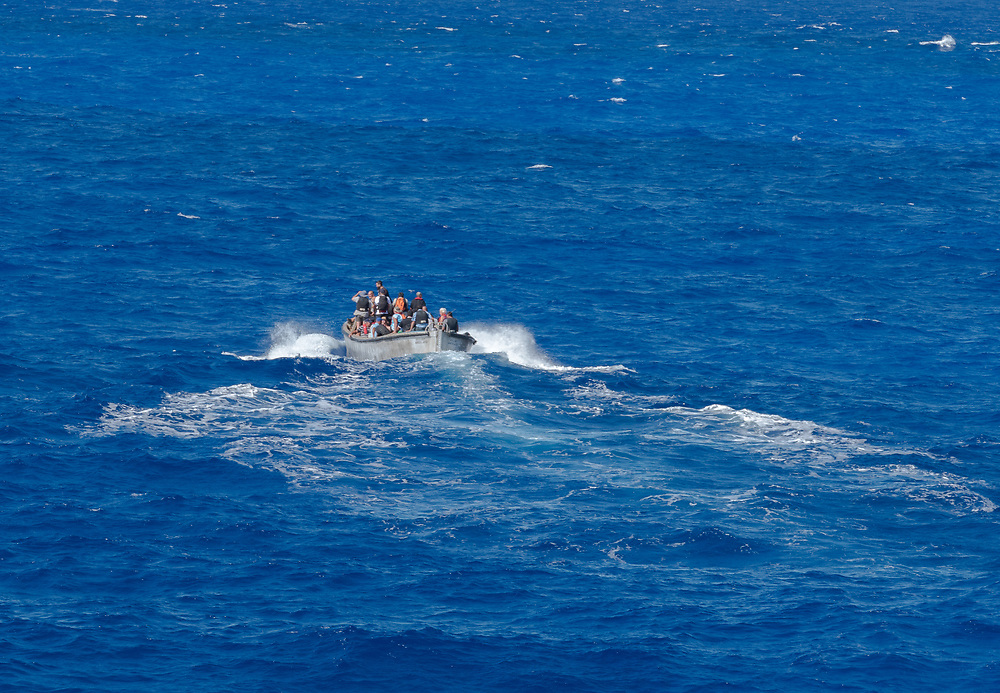 Pitcairn Island, Pacific Ocean-- March 27, 2018.  Natives of Pitcairn Island set sail for home after visiting a nearby cruise ship. Editorial Use Only.