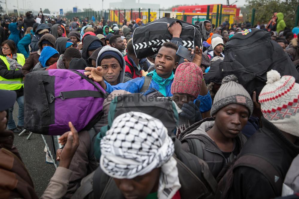 Calais, Pas-de-Calais, France - 24.10.2016    <br />  <br /> Refugees line up at the registration center to get in busses. Start of the eviction on the so called &rdquo;Jungle&quot; refugee camp on the outskirts of the French city of Calais. Refugees and migrants leaving the camp to get with buses to asylum facilities in the entire country. Many thousands of migrants and refugees are waiting in some cases for years in the port city in the hope of being able to cross the English Channel to Britain. French authorities announced a week ago that they will evict the camp where currently up to up to 10,000 people live.<br /> <br /> <br /> Fluechtlinge stehen vor dem Registrierungscenter um in Busse steigen zu koennen. Beginn der Raeumung des so genannte &rdquo;Jungle&rdquo;-Fluechtlingscamp in der franz&ouml;sischen Hafenstadt Calais. Fluechtlinge und Migranten verlassen das Camp um mit Bussen zu unterschiedlichen Asyleinrichtungen gebracht zu werden. Viele tausend Migranten und Fluechtlinge harren teilweise seit Jahren in der Hafenstadt aus in der Hoffnung den Aermelkanal nach Gro&szlig;britannien ueberqueren zu koennen. Die franzoesischen Behoerden kuendigten vor einigen Wochen an, dass sie das Camp, indem derzeit bis zu bis zu 10.000 Menschen leben raeumen werden. <br /> <br /> Photo: Bjoern Kietzmann