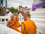 11 JULY 2014 - BANGKOK, THAILAND: Buddhist monks pray at Wat Pathum Wanaram during Asalha Puja Day. Asalha Puja is the day the Lord Buddha preached his first sermon to followers after attaining enlightenment. The day is usually celebrated by merit making and listening to a monks' sermons. It is also day before the start of the Rains Retreat, the three month period when monks stay in their temple for intense mediation and spiritual renewal.    PHOTO BY JACK KURTZ