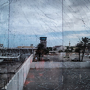 A picture taken through darkened and damaged glass due to a suicide bomb explosion days earlier shows a part of the compound of the Aden Abdulle airport inside the African Union Mission in Somalia (AMISOM) base in Mogadishu, Somalia.