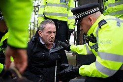 © Licensed to London News Pictures. 07/10/2019. London, UK. A visually Impaired Extinction Rebellion protester is removed from Lambeth Bridge by police. Photo credit: George Cracknell Wright/LNP