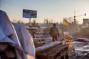 """View from behind the barricades blockading a building supplies store named """"Epicenter"""" in the city of Lviv, Ukraine. Two people passing by."""