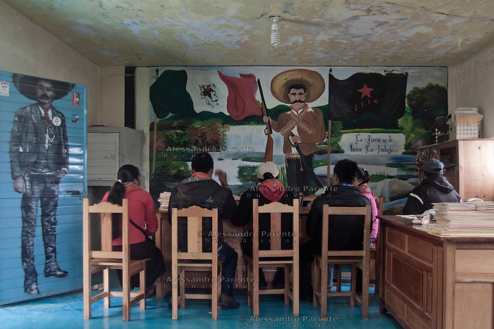 La junta de buen gobierno en reunion, en frente la imagen emblematica de Emiliano Zapata y la escrita &quot;la tierra es de quien la trabaja&quot;.<br /> The good government junta in a reunion. In front the Emiliano Zapata portrait and the writing &quot;the land belongs to those who work on it&quot;
