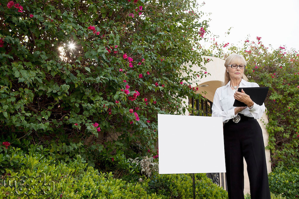 Senior real estate agent standing by sign board reading from clipboard